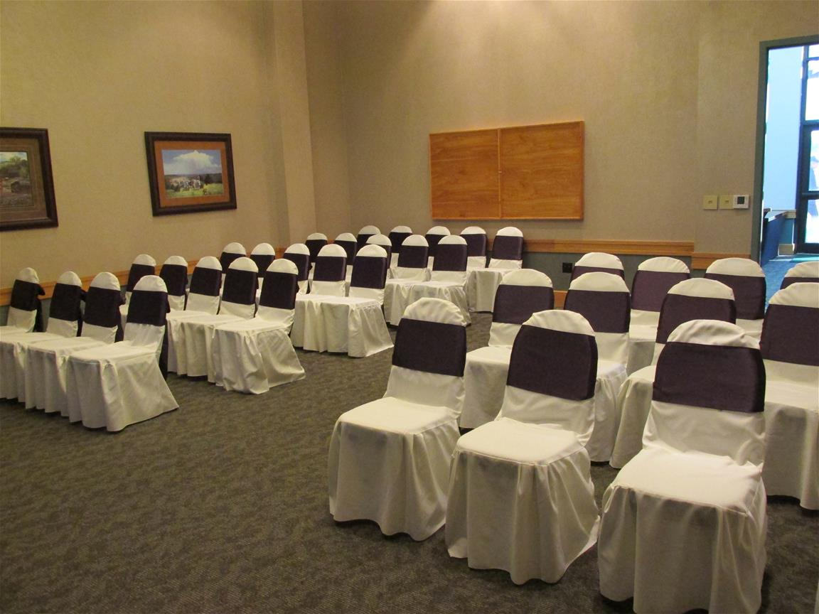 View from the front of the white draped seats with black ties used for a wedding chapel