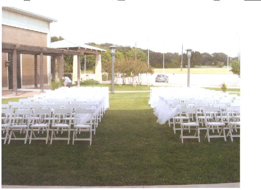 Outside view from the pavilion of chairs in a row wrapped with tool for a wedding