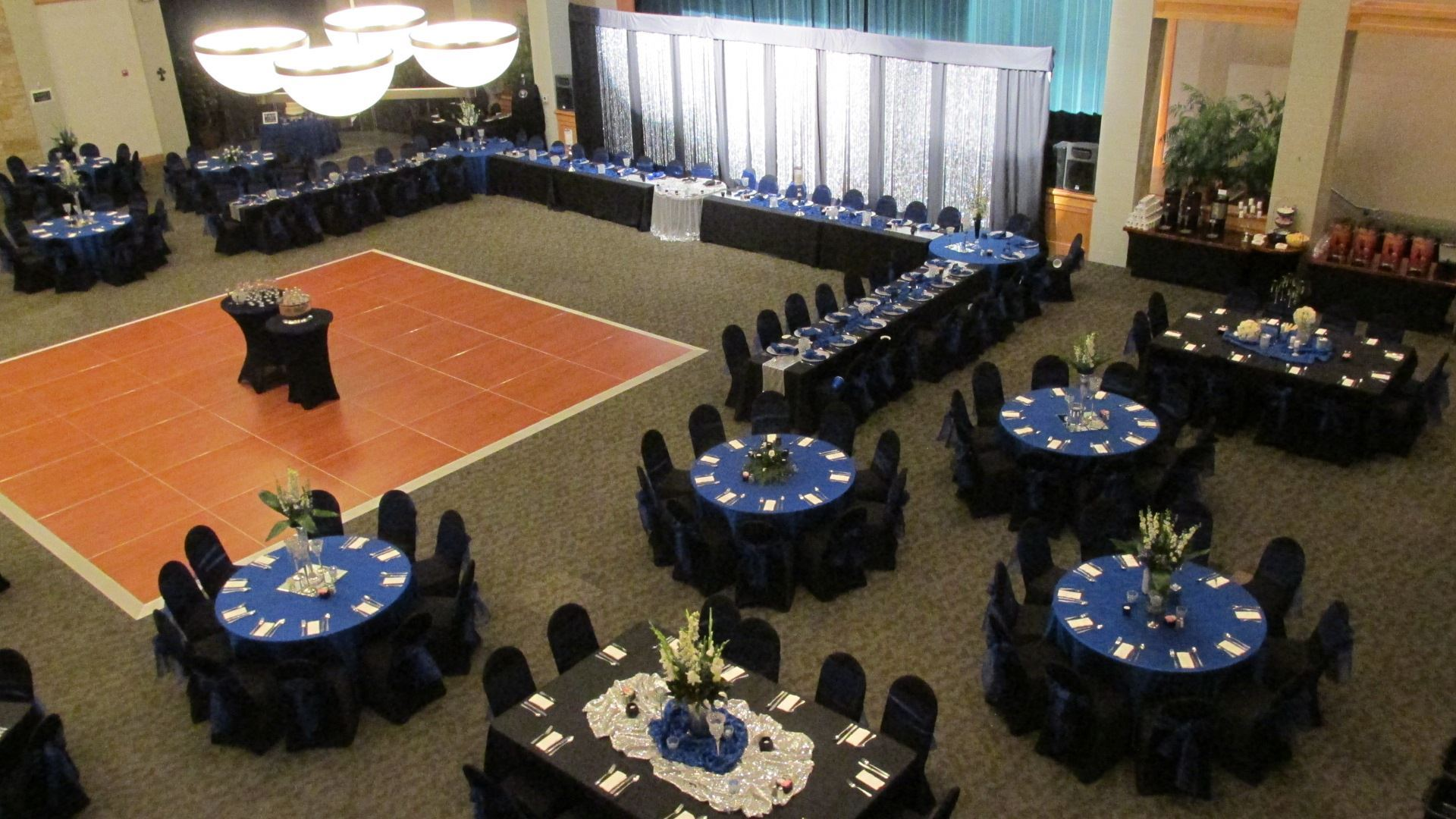 Aerial view of the head table for a royal wedding reception with table placements of black and blue table cloths and white napkins