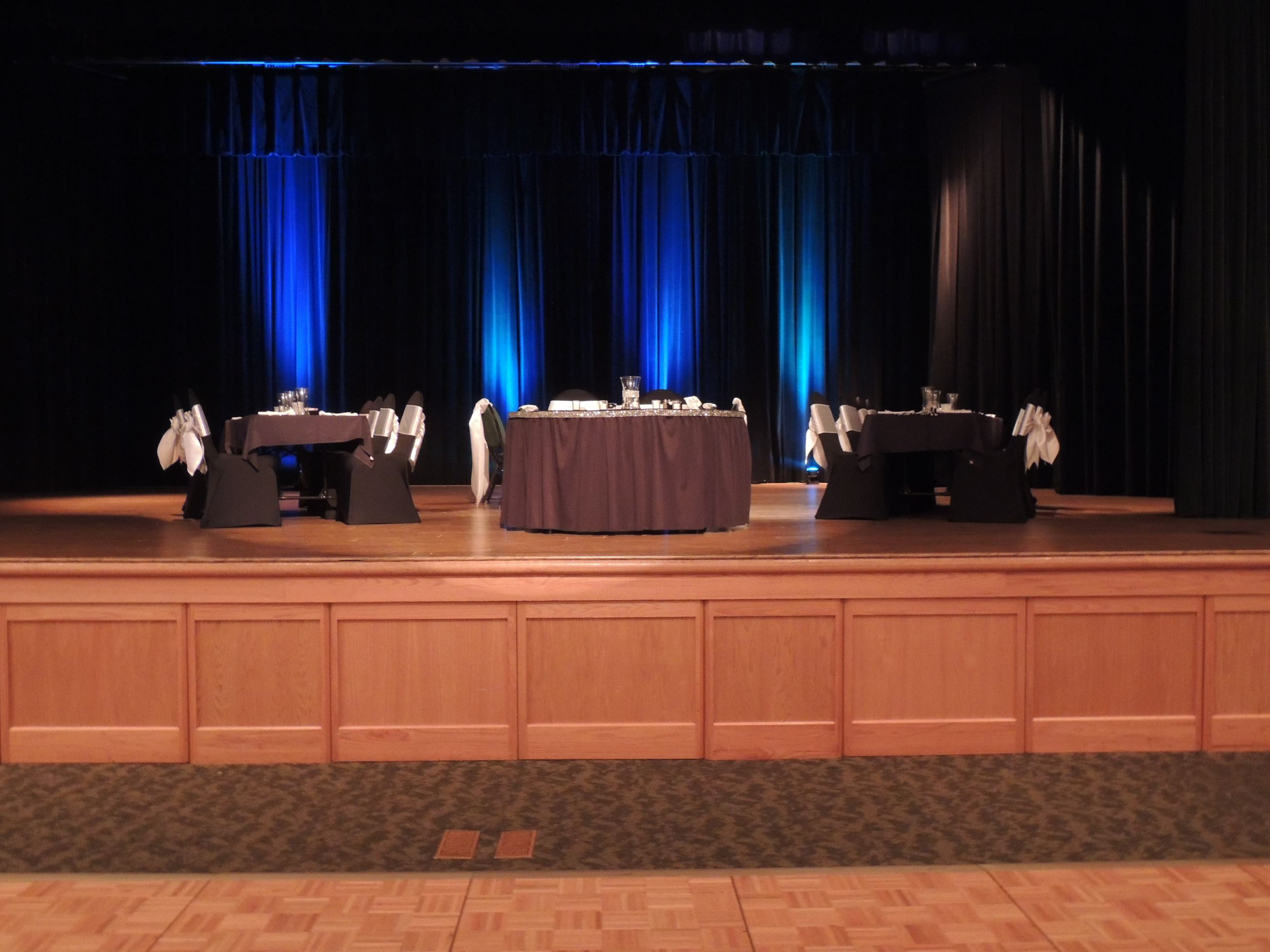 Black and white wedding reception head tables on stage